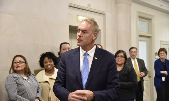 Secretary Zinke wears a suit and stands in a hallway with a small group of employees.