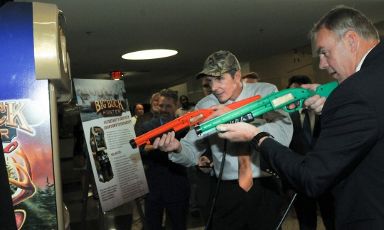 Secretary Zinke and another man hold toy shotguns and play a video game as other people look on.