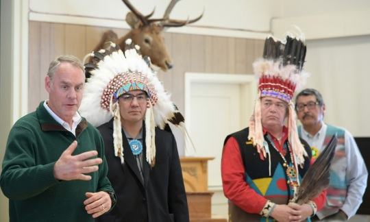 Secretary Zinke stands next to three men wearing traditional Native American clothes.