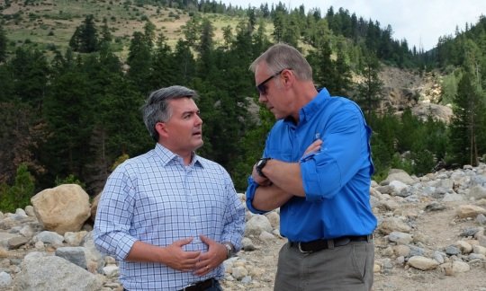 Secretary Zinke, a tall older white man, stands next to Senator Cory Gardner, a shorter white man, on a rocky hillside with a forest behind them.