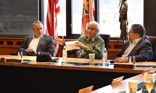 Secretary Zinke, an older white man with gray hair, wears a sport coat and sits at a conference table with two older Native American men.