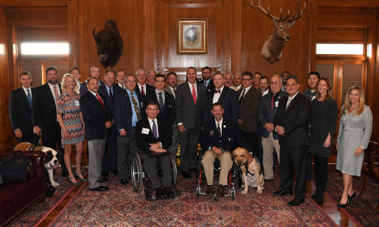 Secretary Zinke poses with a large group of men in suits and a few women in nice dresses in a wood paneled office.