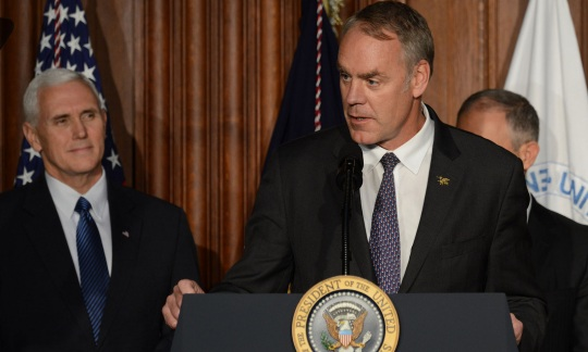 Secretary Zinke wears a suit and stands at a podium with other men standing behind him on stage in an auditorium.