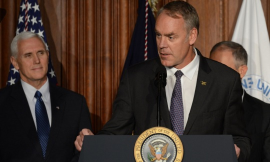 Secretary Zinke wearing a suit and speaking from a podium.