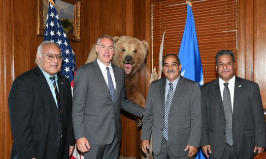Secretary Zinke wears a suit and stands with 3 other men in suits in a wood paneled office next to a stuffed bear.