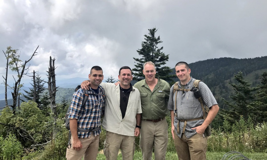 Secretary Zinke and three other white men wearing outdoor gear pose in front of a view of rolling green mountains.