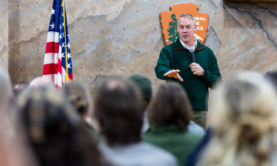 Secretary Zinke holds a microphone and speaks to a group of people sitting inside.