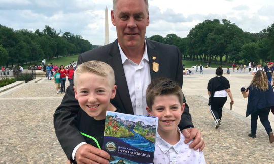 Secretary Zinke, a tall white man with gray hair stands with his arms around two boys and holds up a booklet.