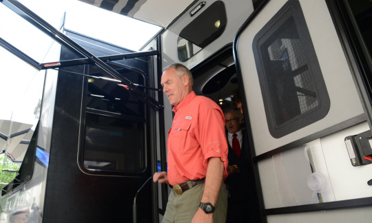 Secretary Zinke in casual clothes stepping out of a large RV.