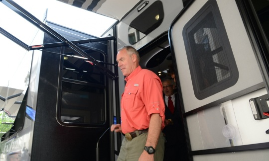 Secretary Zinke, a tall white man with gray hair, steps out of the door of a large RV.