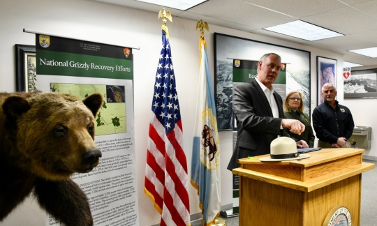 Secretary Zinke, a white man with gray hair, stands behind a podium in a conference room with another white man and a white woman and a stuffed grizzly bear.