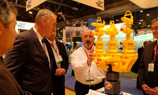 Secretary Zinke, a tall white man with short gray hair talks to a group of people looking at a small plastic model of offshore drilling equipment.