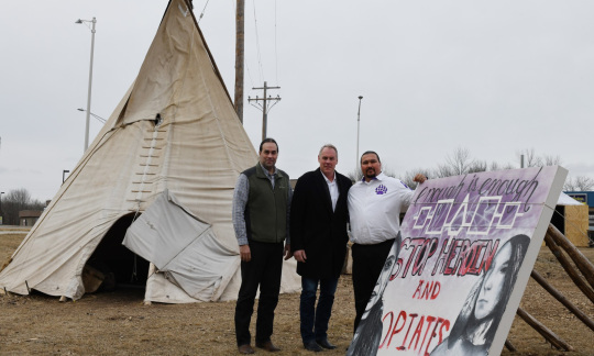 Secretary Zinke stands outside with two Native American men next to a large canvas tipi and a mural calling for an end to heroin and opioid abuse.