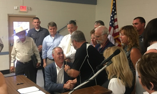 Secretary Zinke sits at a table in a white painted room after signing a piece of paper and holds the pen out to another man while they are surrounded by a small group of cheering people.