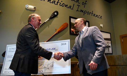 Secretary Zinke, a tall white man with gray hair, stands in a room in front of a large check and shakes hands with a white man with brown hair wearing a sportcoat.