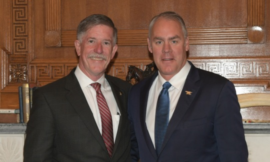 Secretary Zinke and Jim Reilly, both white men with gray hair wearing suits, pose together in a wood paneled office.