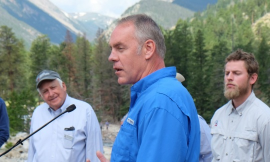 Secretary Zinke wears a blue shirt and speaks to a group of people outside with a forest and mountains in the background.