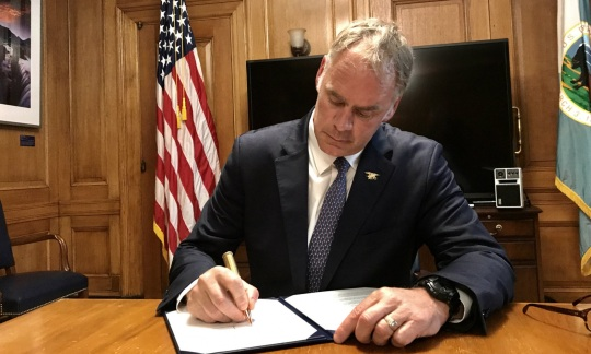 Secretary Zinke wears a suit while sitting at a desk in a wood paneled office and signs a sheet of paper.