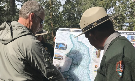 Secretary Zinke wearing a windbreaker looks at large map standing with a male ranger in a National Park Service uniform.