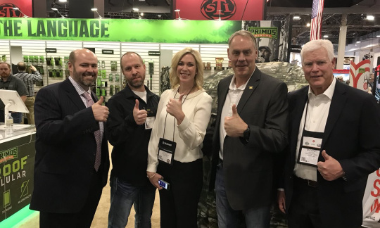 Secretary Zinke stands with a small group of people holding their thumbs up in a large convention hall.