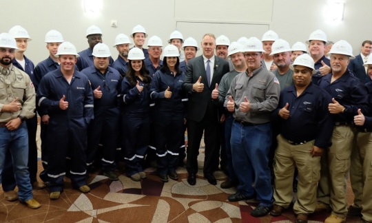 Secretary Zinke wears a suit and poses with a large group of people wearing work clothes and hard hats. They are standing inside, smiling and giving a thumbs up.