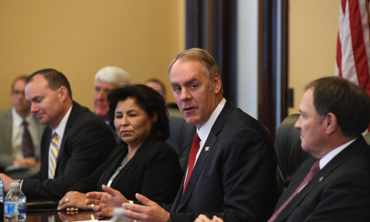 Secretary Zinke sits at a table and talks while other men and women around the table look on and listen.
