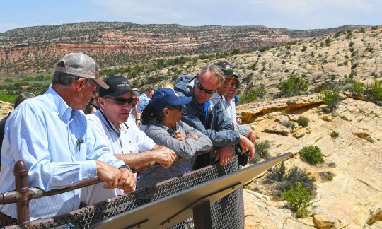 Secretary Zinke and a small group of people stand at a railing overlooking the desert landscape of Bears Ears National Monument in Utah.