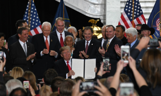 President Trump sits at a table in an ornate white marble rotunda and holds up a large piece of paper while a large group of people stand around him and cheer.
