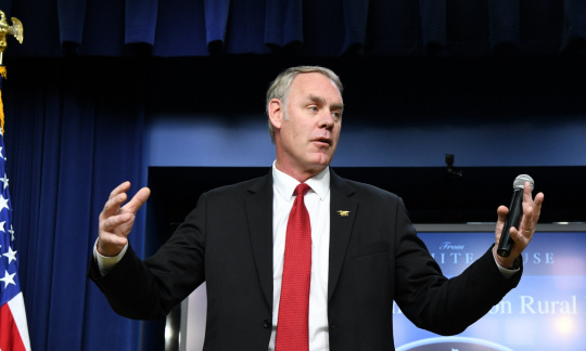 Secretary Zinke, an older white man with short gray hair, wears a suit and stands with his arms outstretched in front of a blue screen.