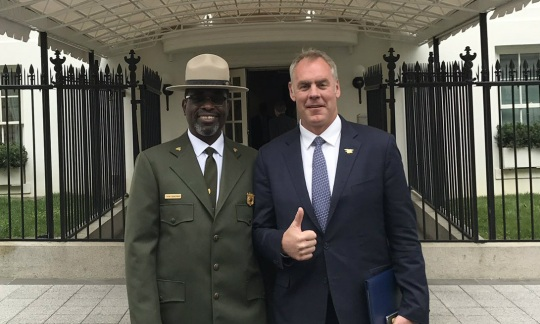 Secretary Zinke wearing a suit stands next to a man in a National Park Service uniform under a white canopy on the White House lawn.