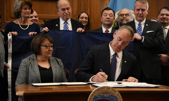 Secretary Zinke signs an agreement surrounded by onlookers