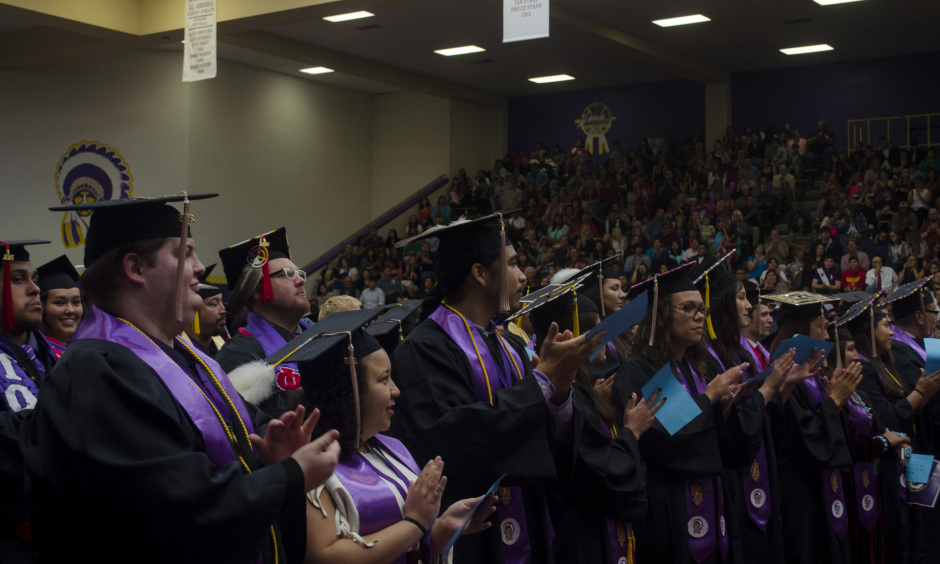 A large group of graduates in black robes and square hats cheer at their graduation ceremony in a large gym.