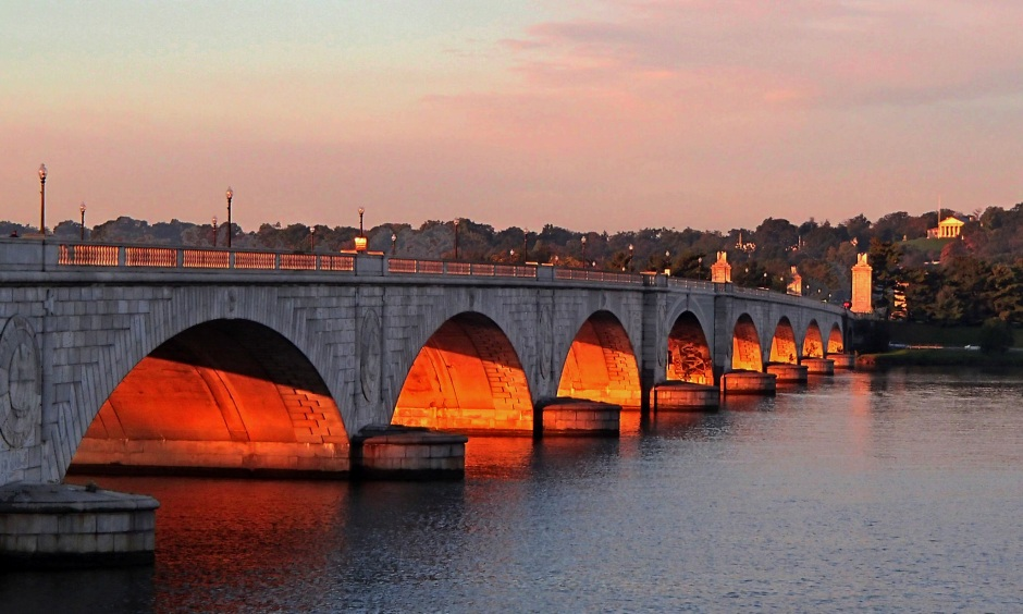 A series of arches carries a bridge over a wide river.