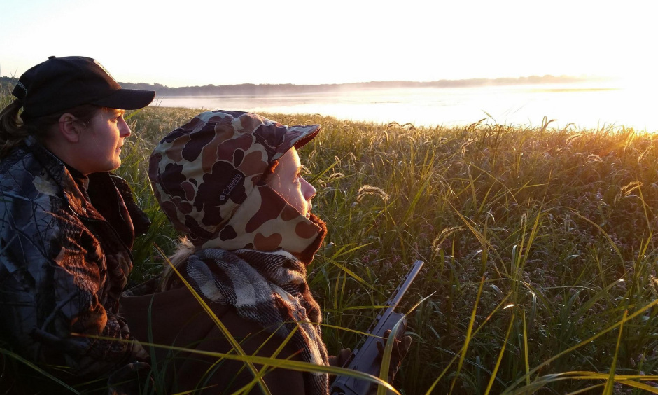 A woman and a young girl holding a shotgun and dressed in hunting gear sit in tall grass by a fog covered lake.