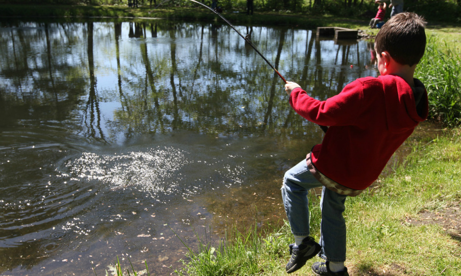 Secretary zinke announces distribution of 11 billion to state a young boy wearing a red sweatshirt stands on the bank of a pond and tries sciox Image collections
