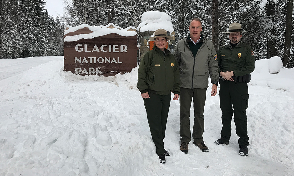 Secretary Zinke and two Park Rangers in front of Glacier National Park sign