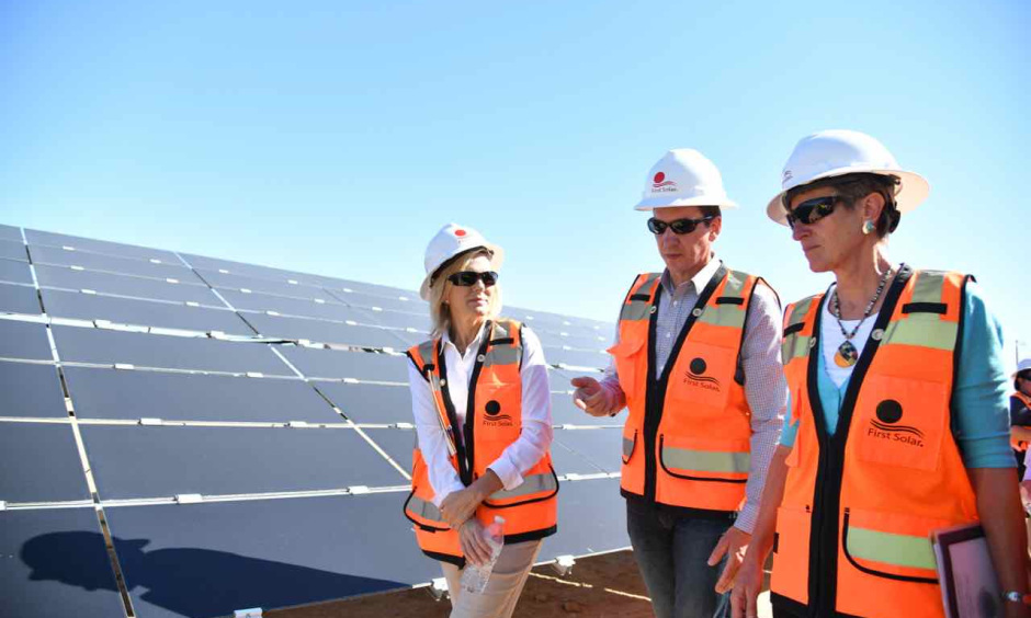 Secretary Jewell and two other people wearing safety vests and hardhats walk by a large solar panel.