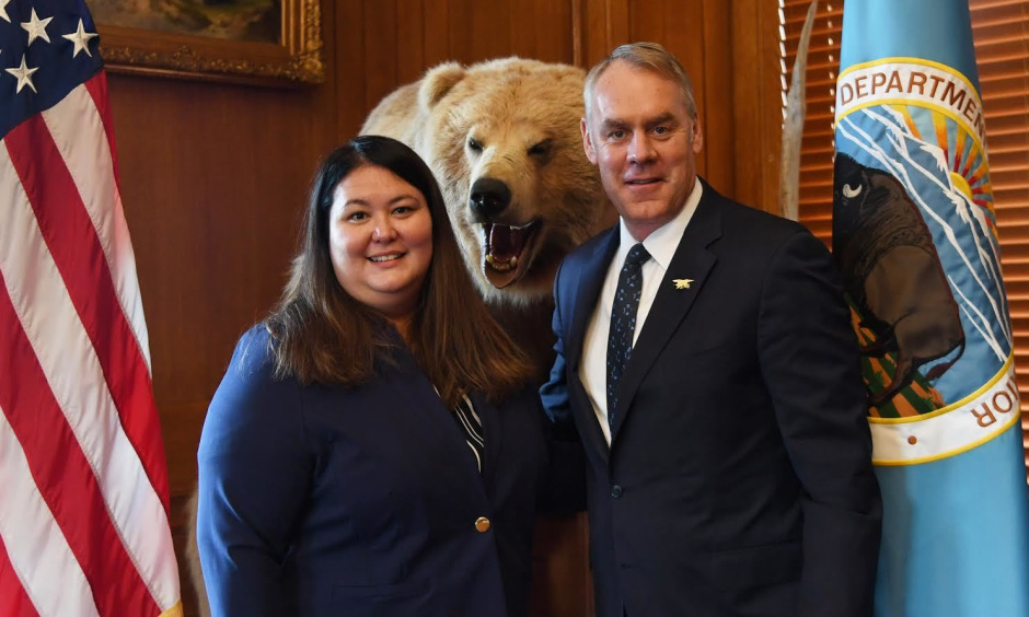 Tara Sweeney stands next to Secretary Zinke with an American flag, stuffed bear and Interior Department flag in the background