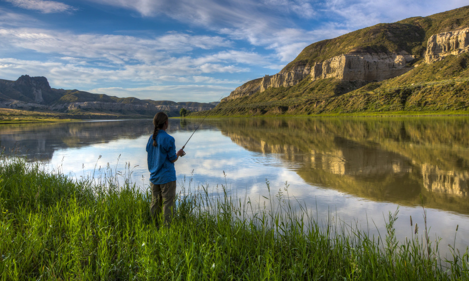 A girl stands on a riverbank useing a fishing pole to fish in a wide river.