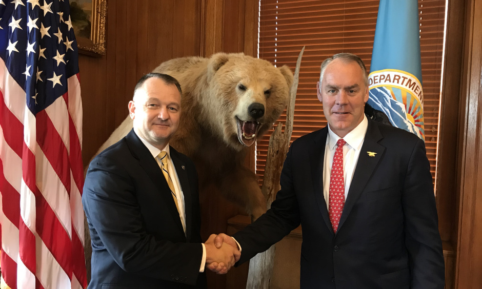 Secretary Zinke shakes hands with Cam Sholly in front of flags in wood panel office.
