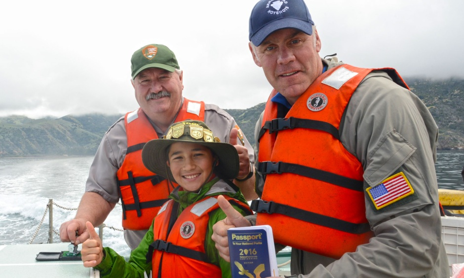 Secretary Zinke with a park ranger and a young boy standing on a boat moving through the water. All are wearing life vests.