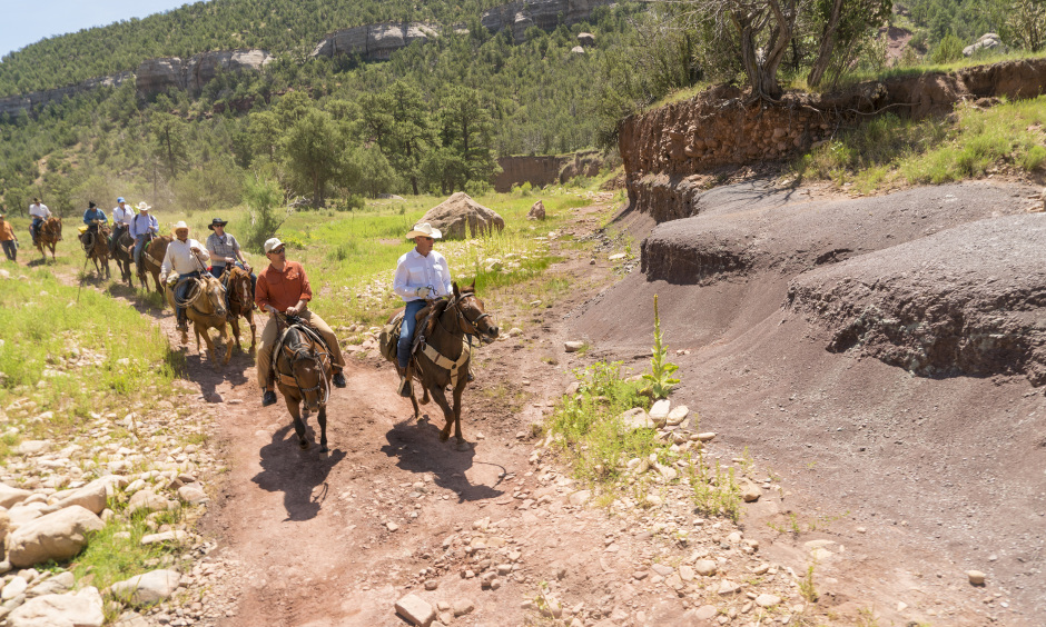 Secretary Zinke and a group of people ride on horseback through the rocky Sabinoso Wilderness.