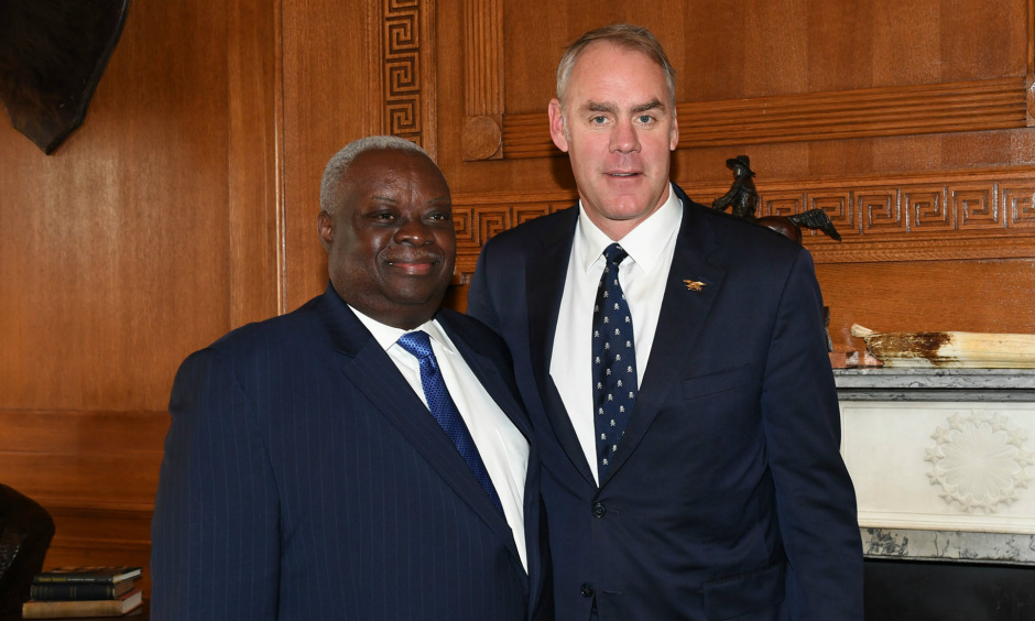 Secretary Zinke and Governor Mapp wear suits and pose for a photo in a wood paneled office.