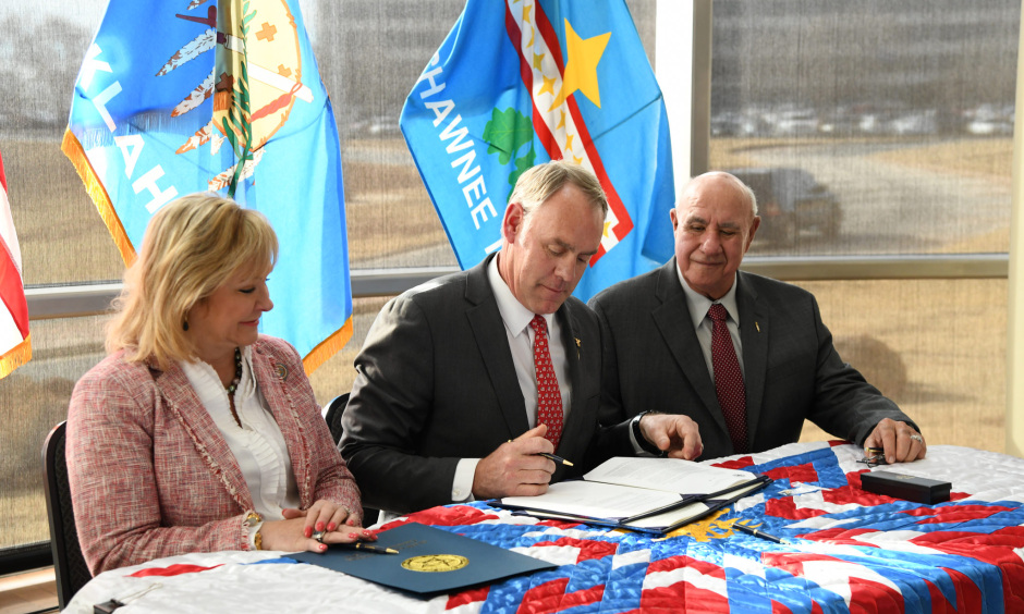 Secretary Zinke wears a suit and signs a piece of paper while sitting at a table with flags behind him and a woman and man sitting on either side of him.