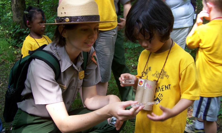 An NPS ranger and a little girl examine insects.