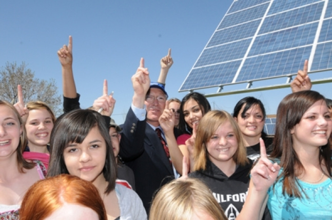 Secretary Salazar stands with Milford High Students in front of a newly installed solar panel.