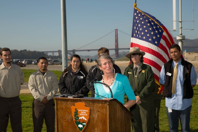 Jewell Speaks at podium with flag and Golden Gate Bridge in the background