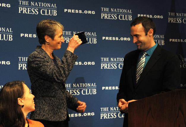 Jewell holds a National Press Club mug