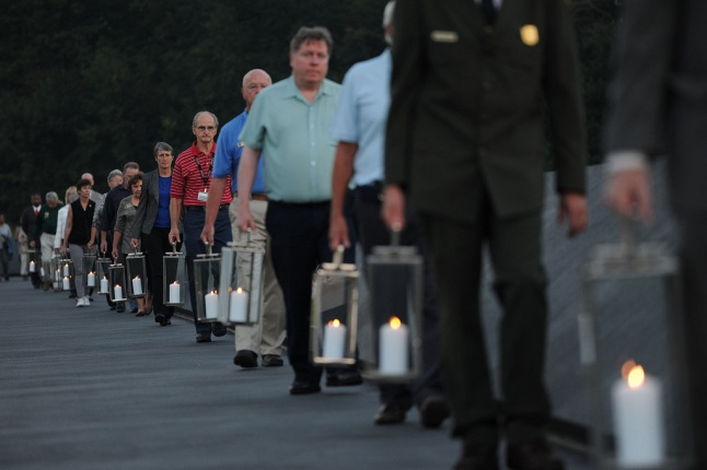 A line of people holding lanterns in the Flight 93 National Memorial