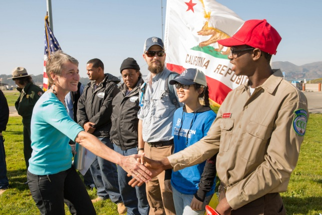 Secretary Jewell shaking hands with a young conservation corp member